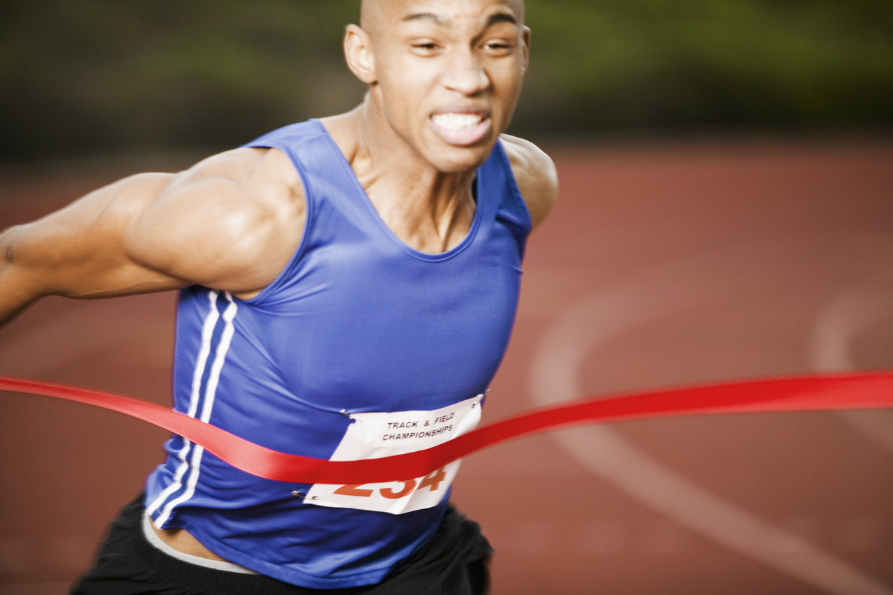 Athlete Running Through Finish Line