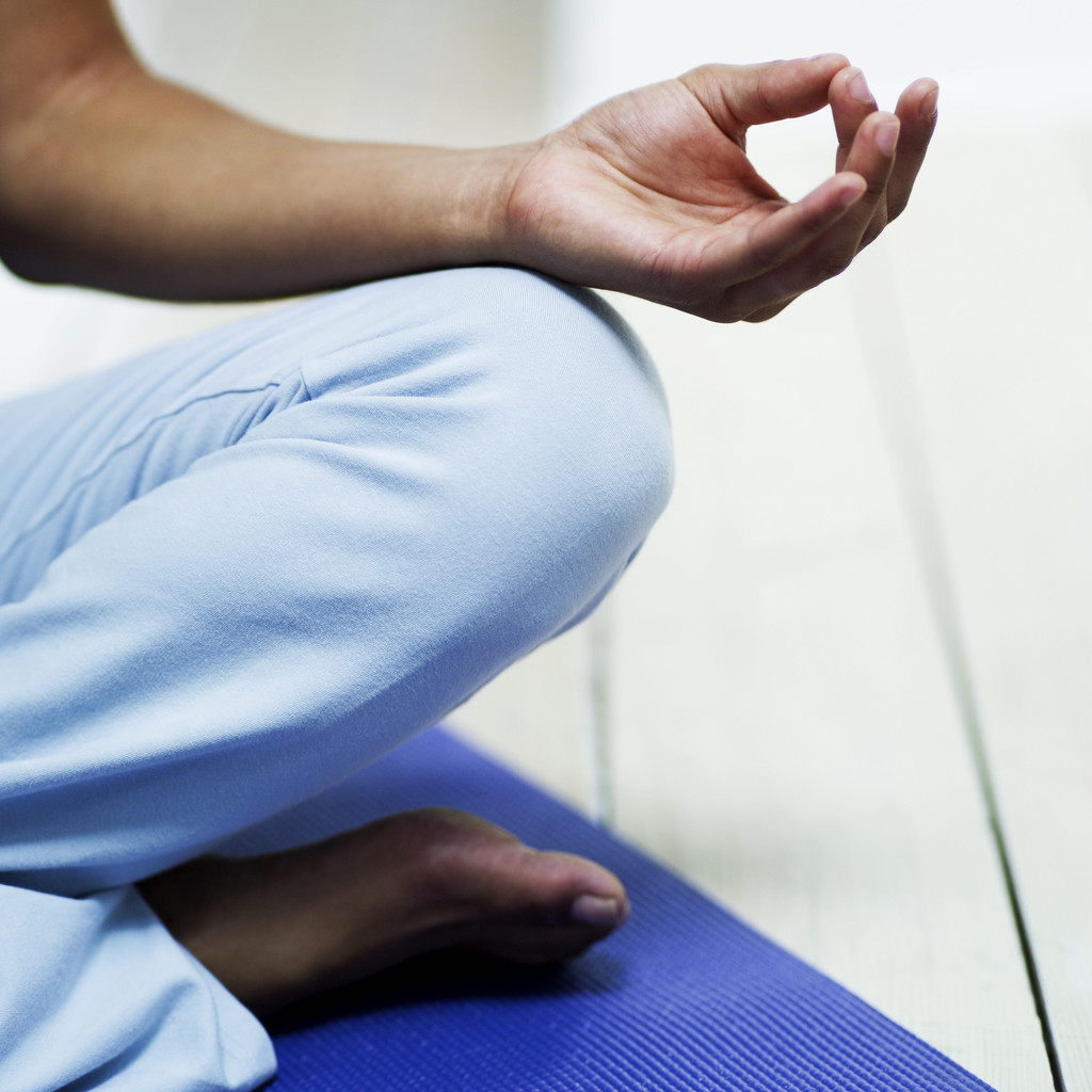 Young Woman Meditating on the Floor