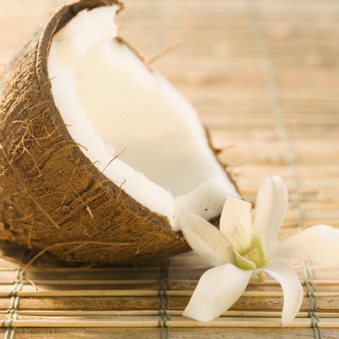 Half Coconut and Flower on Bamboo Mat --- Image by © Royalty-Free/Corbis